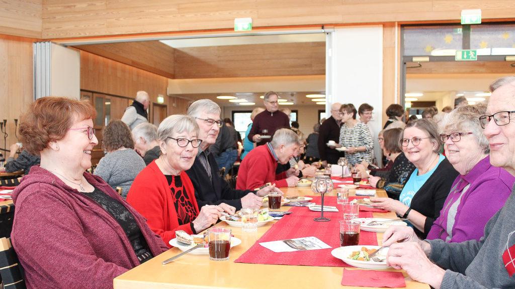 Ryhmä aikuisia ruokailemassa pitkän pöydän ääressä.