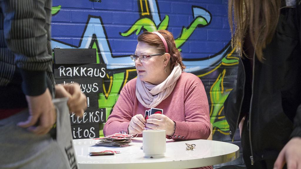 Nainen pöydän ääressä pelikortit kädessään, taustalla graffitiseinämaalaus