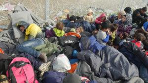 Pakolaisiksi joutuneita ihmisiä makaa kasassa makuupusseissaan.